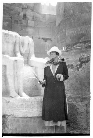 H.D., Egypt, 1923. Photo courtesy of Norman Holmes Pearson and New Directions Publishing Corp. Image shows H.D. with hat and scarf standing before the partial statue of a seated couple in ruins in Egypt.