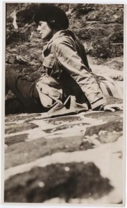 Photograph of H.D. in pants and a jacket leaning back, seated on a blanket on a rocky hill. Undated. From Beinecke Library, Digital Collections, H.D. Papers.
