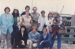 Photo of participants at the HD Centennial Conference in Orono, Maine, 1986. Participants pose for photo on a dock with boats in the background. Pictured from left to right: (front) Anne Friedberg, Charlotte Mandel, Cyrena Pondrom, (back row) Eileen Gregory, Cassandra Laity, (2 participants unidentified), Joe Milicia, Dee Morris, Susan Friedman, Rachel DuPlessis (with child). Photo by Cassandra Laity.