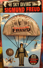 "Photo of a Sigmund Freud doll wearing a parachute with the label ""Sky Diving Sigmund Freud"" printed on the chute."
